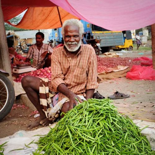 A smiling man in an orange checked button up shirt and striped dhoti sells long green beans in a vegetable market outside of Madurai.