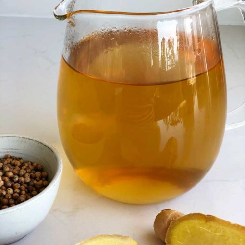 Sukku Coffee sits in a glass pot. Ginger and whole coriander seeds garnish.